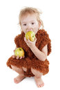 Little funny Neanderthal boy in a suit with dirty face eating an apple. Royalty Free Stock Photo