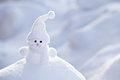 Little funny white snowman in the snowbank Royalty Free Stock Image