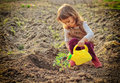 Little gardener girl watering plants in a garden Stock Photos