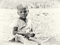 Little Ghanaian girl sits on the ground Stock Images