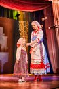 A little girl and an adult woman in Russian national dress rehearsing on stage. Mother and daughter sing and dance together