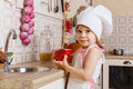 Little girl in apron in the kitchen and cap of cook with an apple stands near sink at home mother s helper year old Stock Image