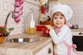 Little girl in apron in the kitchen and cap of cook with an apple stands near sink at home mother s helper year old Royalty Free Stock Photo
