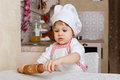 Little girl in apron in the kitchen and cap of cook with rolling pin sits at dining table house mother s helper Stock Photography