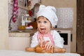 Little girl in apron in the kitchen and cap of cook with rolling pin sits at dining table house mother s helper Stock Images