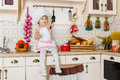 Little girl in apron in the kitchen and cap of cook sits house mother s helper year old Stock Photos