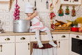 Little girl in apron in the kitchen and cap of cook sitting house mother s helper year old Stock Images