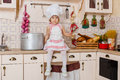 Little girl in apron in the kitchen and cap of cook sitting house mother s helper year old Royalty Free Stock Image