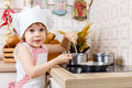 Little girl in apron in the kitchen and cap of cook stands near cooker house mother s helper year old Royalty Free Stock Images