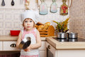 Little girl in apron in the kitchen and cap of cook stands near cooker house mother s helper year old Stock Photo