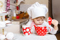 Little girl in apron in the kitchen and cap of cook with sweet desserts sits at dining table house mother s helper Stock Image