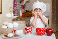 Little girl in apron in the kitchen and cap of cook with sweet desserts sits at dining table house mother s helper Stock Photos