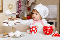 Little girl in apron in the kitchen and cap of cook with sweet desserts sits at dining table house mother s helper Royalty Free Stock Images