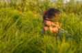Little girl as indian  hiding behind grass Royalty Free Stock Photo