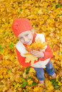 Little girl with autumn leaves Stock Images