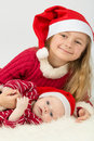 Little girl with baby boy lie in hats of santa claus smiling the Stock Photos