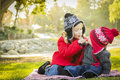 Little girl with baby brother wearing coats and hats outdoors her winter sharing a lollipop at the park Royalty Free Stock Image