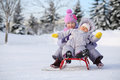 Little girl and baby dressed near forest sit on red sled in warm clothes at winter Royalty Free Stock Photography