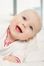Little girl baby laying under white blanket adorable looking out a cover on window background Stock Photography