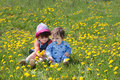 Little girl and baby with pacifier sit on meadow green yellow dandelions Stock Photos