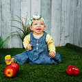 Little girl in the backyard sits on a lawn and smiling at her feet lie apples Stock Image