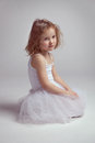 Little girl - ballerina tired and sitting on the floor Royalty Free Stock Photo