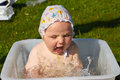 Little girl bathes in a basin on the nature Royalty Free Stock Photo