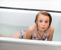 Little girl bathes in a bathroom eight years old and cheerfully laughs Royalty Free Stock Photography