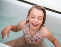 Little girl bathes in a bathroom eight years old and cheerfully laughs Stock Photography