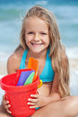 Little girl on the beach with small bucket and shovels for sand portrait Stock Photos