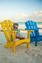 Little girl in beach wooden colorful chairs on tropical tulum mexico Royalty Free Stock Photos