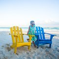 Little girl in beach wooden colorful chairs on tropical tulum mexico this image has attached release Stock Images