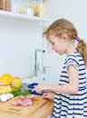 Little girl beats meat. Royalty Free Stock Photo