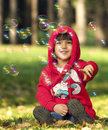 Little girl beautiful with a hood enjoys soap bubbles Stock Images