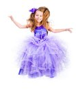Little girl in a beautiful purple dress happy jump on white background Royalty Free Stock Image