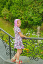 Little girl beautiful standing near railing at summer green park Royalty Free Stock Images