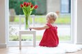 Little girl with beautiful tulips pretty blonde toddler playing standing on the tiles floor next to a big window street view Royalty Free Stock Photo