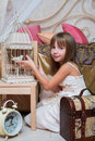 Little girl in the bedroom playing with a bird cage Stock Images
