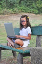 Little girl on a bench with computer and glasses Royalty Free Stock Photo