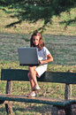 Little girl on a bench with computer Royalty Free Stock Photo