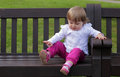 Little girl on the bench sitting in a park Royalty Free Stock Photos