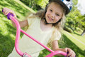 Little girl on a bicycle at summer park close up portrait of Stock Photos