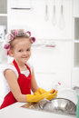 Little girl with big curls doing the dishes smiling wearing large gloves Royalty Free Stock Photo