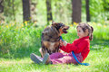 Little girl with big dog in the forest happy sitting lawn Stock Image