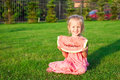 Little girl with big piece of watermelon in hands on green grass this image has attached release Stock Photography