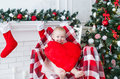 Little girl with big red heart sits in a chair near the Christmas tree