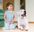 Little girl with big white dog cute lying on the floor at home focus on Stock Photo