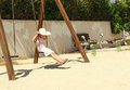 Little girl in a big white hat having fun on a swing at sunny day Royalty Free Stock Photo