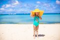 Little girl in big yellow hat on white sandy beach Royalty Free Stock Photo