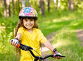 Little girl on bike in forest looking at camera and smiling Royalty Free Stock Photo